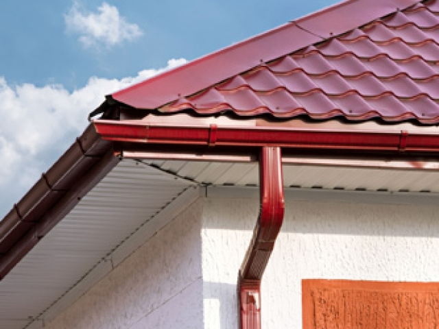 House roof, gutters and downspout on the corner of a house
